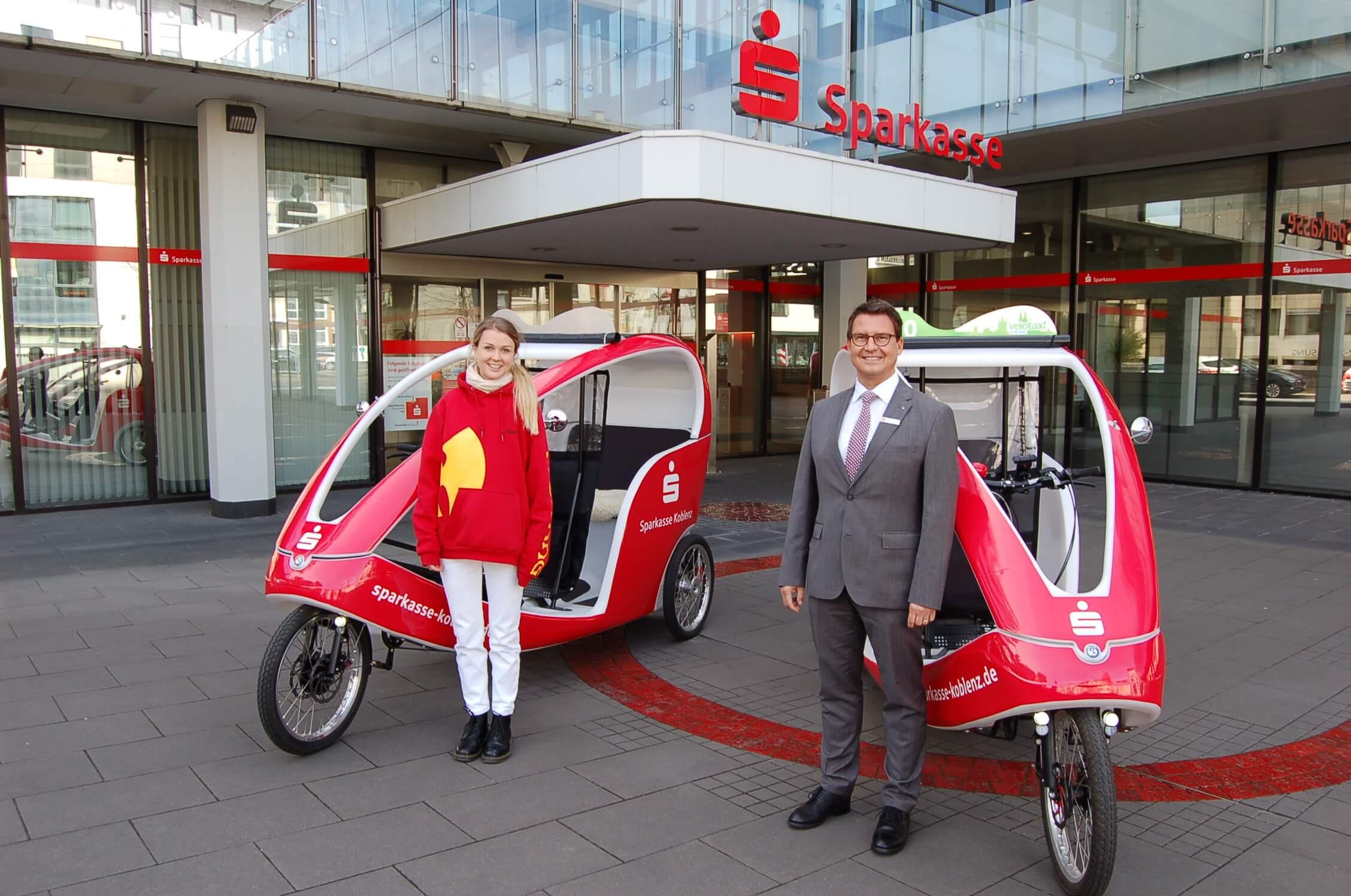 Jungunternehmerin Jule Sabel (links) und Sparkassenchef Matthias Nester bei der Präsentation der Velotaxis vor der Hauptstelle der Sparkasse.