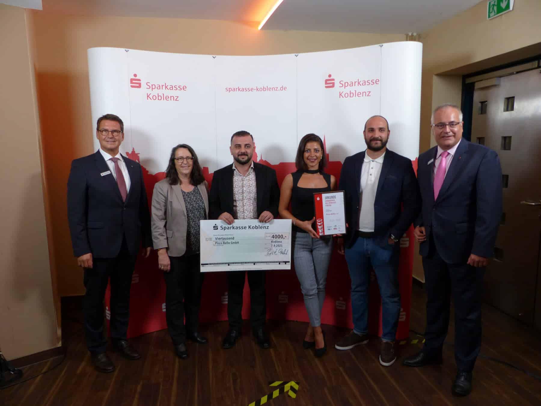 Sparkassenchef Matthias Nester (links) gratuliert zusammen mit Vorstand Jörg Perscheid (rechts) dem Gewinnerunternehmen Picco Bello GmbH aus der Kategorie